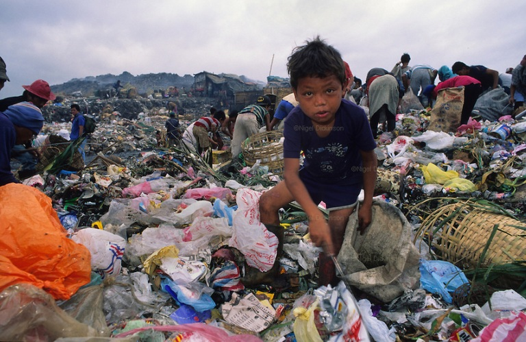 A child picks trash for income on a dumpsite. Photo by Nigel Dickinson.