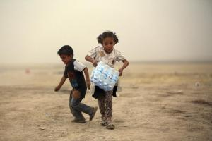 A girl, who fled from the violence in Mosul, carries a case of water at a camp on the outskirts of Arbil in Iraq's Kurdistan region, June 12, 2014. Stringer/Iraq / Reuters
