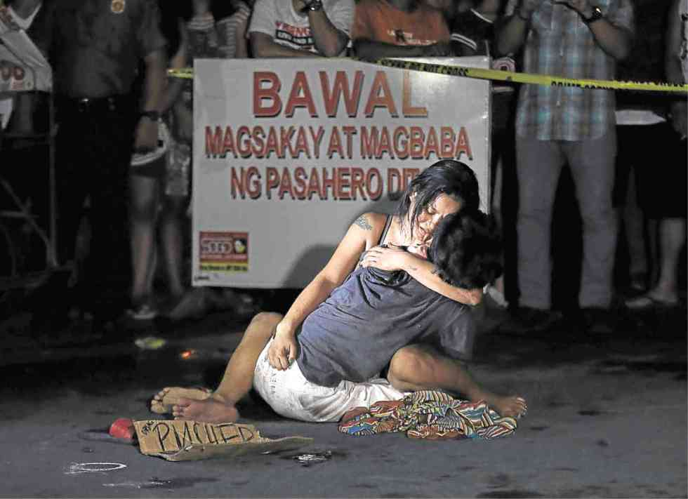 LAMENTATION A weeping Jennelyn Olaires hugs partner Michael Siaron, 30, a pedicab driver and alleged drug pusher, who was shot and killed by motorcycle-riding gunmen near Pasay Rotonda on Edsa. He was one of six killed in drug-related incidents in Pasay and Manila yesterday. RAFFY LERMA www.inquirer.net